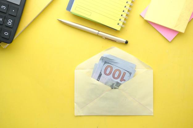Gros plan sur de l'argent en dollars américains dans une enveloppe sur une surface jaune