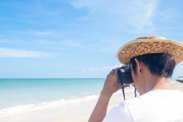 Gros plan, arrière, vue, homme asiatique, tir, photo, sur, plage, bonnes vacances