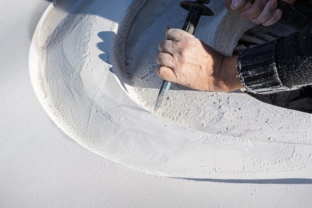 Gros plan d'un artiste sculptant des courbes dans une pierre blanche avec des gestes précis à l'aide d'un ciseau
