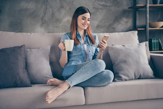 Gros plan assez adorable foxy lady s'asseoir divan boire du café chat téléphone