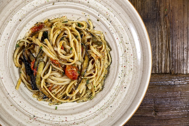Gros plan d'une assiette blanche pleine de spaghettis et de légumes sur une surface en bois