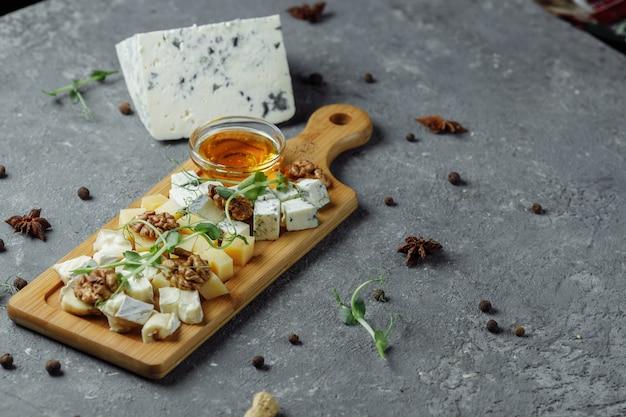 Gros plan d'une assiette de fromages. 4 types de fromage, fromage brie blanc à pâte molle, camembert, briques semi-tendres, bleu, roquefort, fromage à pâte dure. noix, raisins verts. beau service. restaurant.