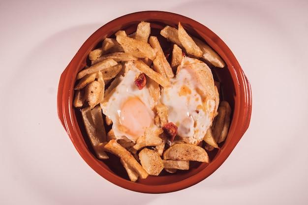 Gros plan d'une assiette d'œufs brouillés ou d'œufs avec mise au point sélective de chorizo et chips