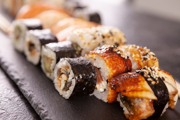 Gros plan sur une assiette de sushis sur pierre sombre. foos asiatiques en bonne santé