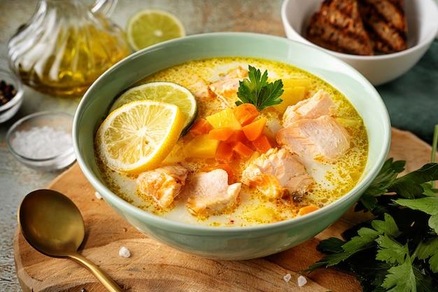 Gros plan d'une assiette verte avec une délicieuse soupe de poisson au saumon avec de la crème végétale sur planche de bois avec des ingrédients autour