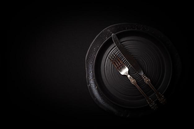 Gros plan des assiettes en céramique noires rondes vides, fourchette en argent, couteau sur fond sombre