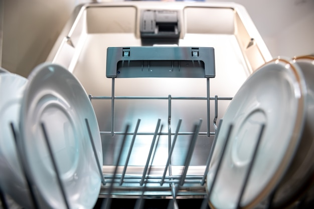 Gros plan sur des assiettes propres à l'intérieur du lave-vaisselle.