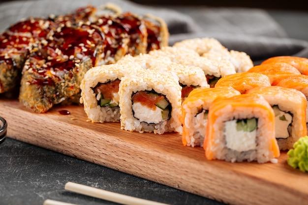 Gros plan sur un assortiment de rouleaux de sushi sur une planche en bois avec wasabi et sauce soja