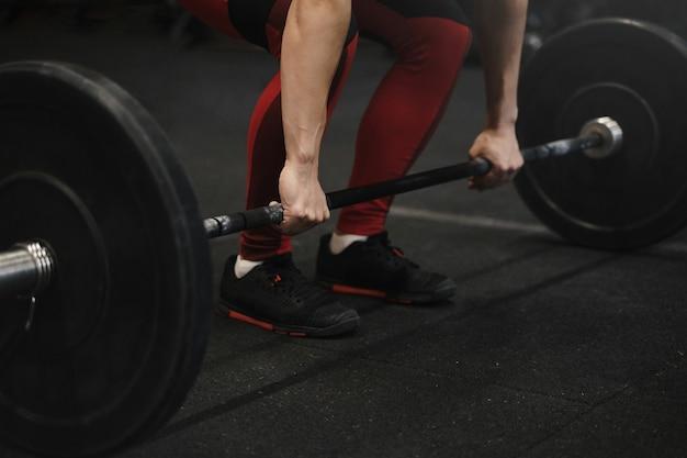 Gros plan d'une athlète féminine se préparant à soulever des poids au gymnase.