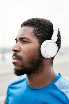 Gros plan d'un athlète sérieux dans des écouteurs sans fil écoutant de la musique pendant l'entraînement sportif à l'extérieur