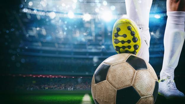 Gros plan d'un attaquant de football prêt à botter le ballon au stade