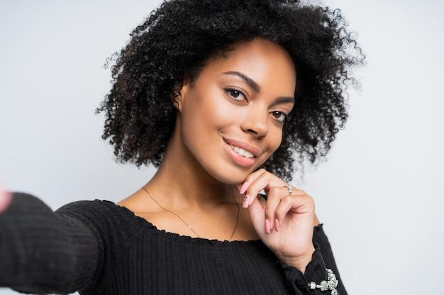 Gros plan autoportrait d'une belle femme afro-américaine prenant un selfie.
