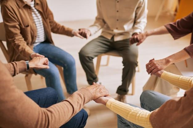 Gros plan aux tons chauds de personnes se tenant la main en cercle pendant la séance de thérapie dans un groupe de soutien, espace de copie