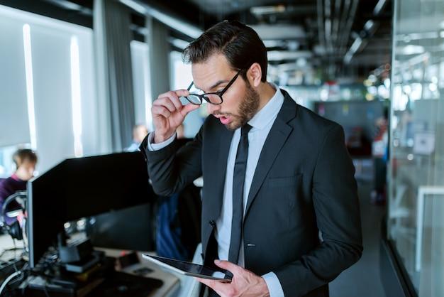 Gros plan d'un avocat prospère chaussé habillé en tenue de soirée debout devant son bureau et à l'aide de tablette pour le travail.
