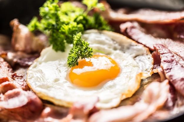 Gros plan de bacon rôti et d'œufs aux herbes dans une casserole.