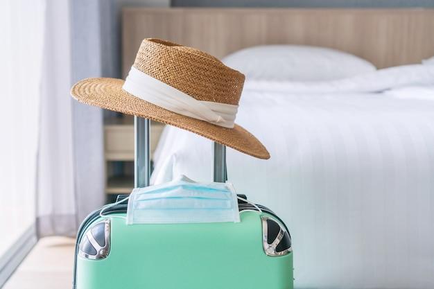 Gros plan de bagages verts, chapeau de paille et masque chirurgical. voyager dans un nouveau concept de mode de vie normal.