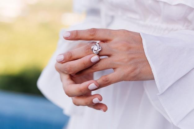 Gros plan d'une bague en diamant élégante en doigt de femme.