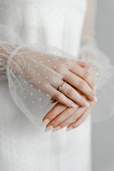Gros plan d'une bague en diamant élégante sur le doigt avec fond gris écharpe. bague en diamant bague de mariage avec main.mains féminines, la mariée a plié ses mains