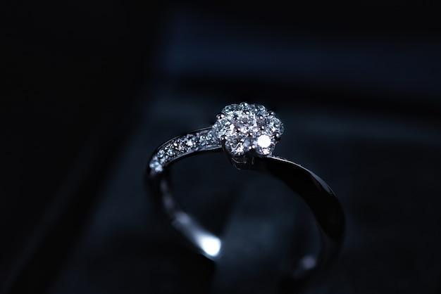 Gros plan d'une bague en diamant sur fond sombre