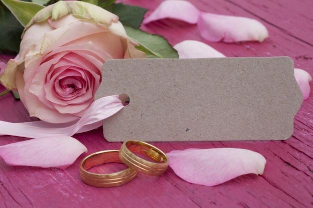 Gros plan de bagues de fiançailles, une étiquette et de belles roses roses sur la table