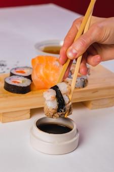 Gros plan sur des baguettes prenant une portion de rouleau de sushi et de sauce soja.