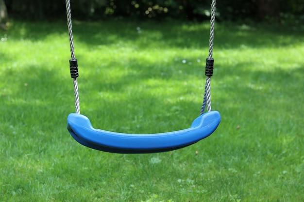 Gros plan d'une balançoire bleue avec de l'herbe verte en arrière-plan