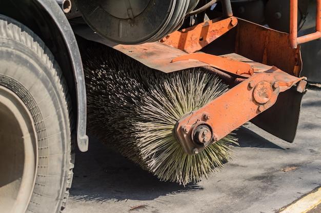 Gros plan d'une balayeuse de nettoyage de rues lave la route goudronnée