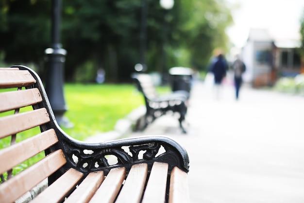 Gros plan sur un banc en bois vert dans un parc urbain pendant l'heure du coucher du soleil. banc en bois vide dans le parc de la ville