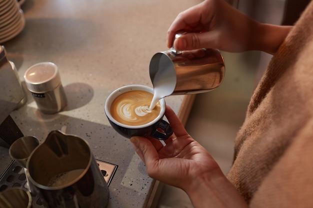 Gros plan d'un barista méconnaissable créant de l'art latte avec de la crème tout en préparant du café frais dans un café ou un café, espace de copie