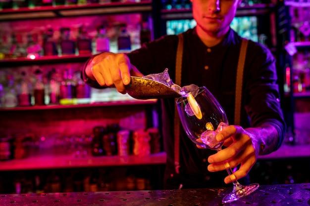 Gros plan sur un barman qui termine la préparation d'un cocktail alcoolisé, versant un verre à la lumière du néon