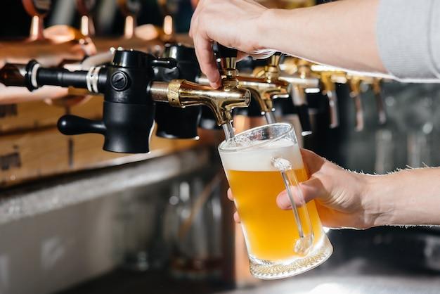 Gros plan sur le barman remplissant une chope de bière légère. le comptoir du bar dans le pub.
