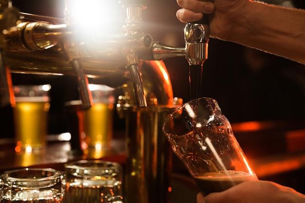 Gros plan d'un barman versant de la bière