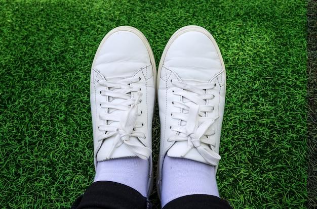 Gros plan de baskets blanches sur la surface de l'herbe
