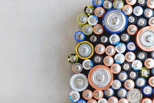 Gros plan des batteries déchargées colorées de différentes tailles, formats, vue de dessus