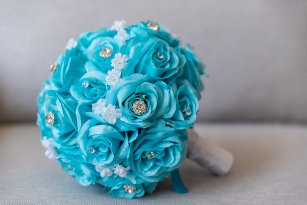 Gros plan d'un beau bouquet de mariage fait de fleurs bleues et de bijoux