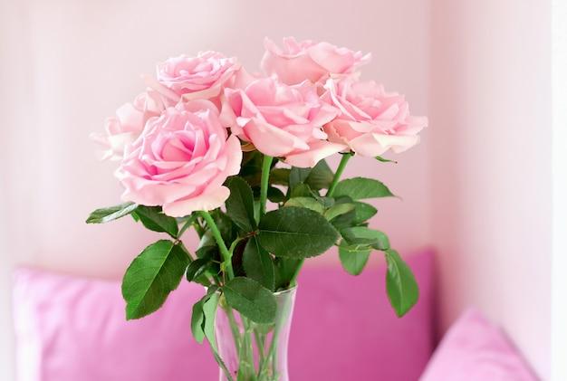 Gros plan d'un beau bouquet de roses roses dans un vase en verre sur table au salon.