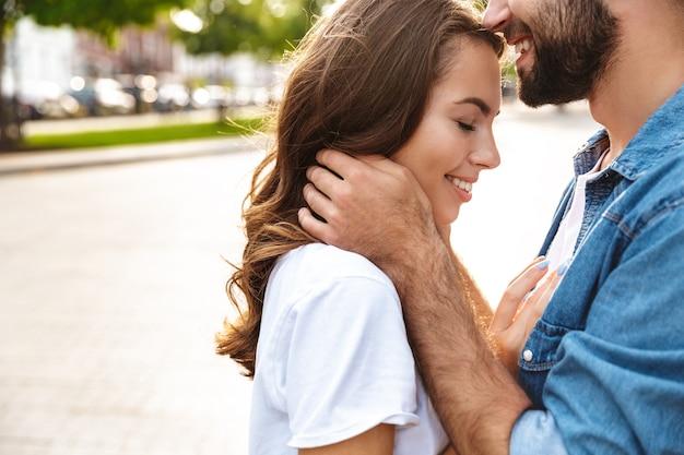 Gros plan d'un beau jeune couple amoureux marchant à l'extérieur dans la rue de la ville, embrassant