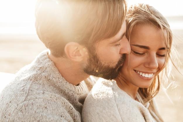 Gros plan d'un beau jeune couple souriant embrassant tout en se tenant à la plage
