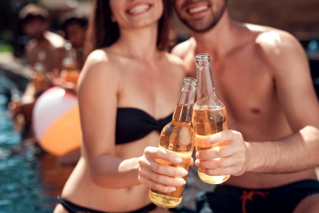 Gros plan, beau, jeune couple, tenue, bouteilles bière