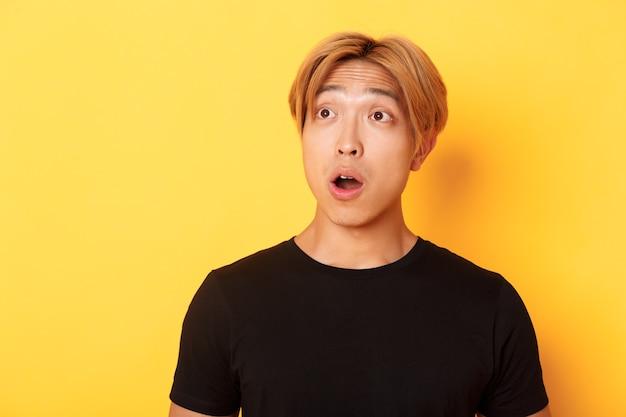 Gros plan d'un beau mec asiatique impressionné, regardant le coin supérieur gauche avec la mâchoire tombée et la stupéfaction, debout sur le mur jaune.