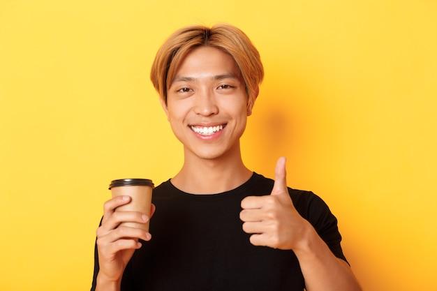 Gros plan d'un beau mec asiatique satisfait recommande un café, tenant une tasse de café et montrant le pouce en l'air en approbation, souriant heureux sur un mur jaune