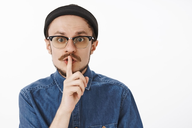 Gros plan d'un beau mec paniqué inquiet avec barbe en bonnet noir et lunettes shushing fixant inquiet demandant de garder le silence ou de ne pas dire le secret à quiconque