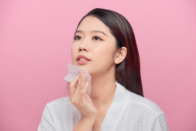 Gros plan d'un beau modèle de fille asiatique heureuse avec un maquillage naturel à l'aide de feuilles absorbant l'huile