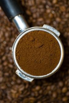 Gros plan, beau porte-filtre expresso plein de marc de café arabica fin