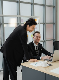 Gros plan beau sourire d'homme d'affaires caucasien et regardant la caméra heureux de travailler avec une femme d'affaires utilisant un ordinateur portable. humeur positive travaillant ensemble avec le partenariat. relation de collègue au bureau.