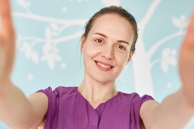 Gros plan de beau sourire jeune femme vêtue de t-shirt violet décontracté
