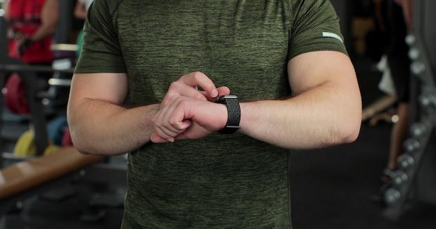 Gros plan beau sportif vérifiant les résultats dans le centre de remise en forme. homme sérieux de remise en forme regardant une montre-bracelet dans un club de sport. sport, fitness, concept de soins de santé.