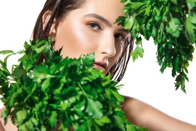 Gros plan sur un beau visage féminin avec un traitement biologique sur fond blanc.