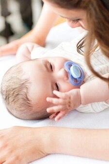 Gros plan d'un bébé allongé sur une table à langer pendant que sa mère change sa couche