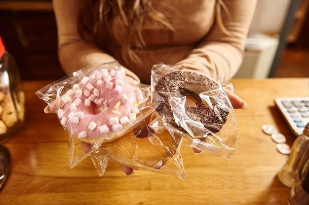 Gros plan de beignets avec diverses glaçures sur les mains du barista sur le fond de la surface en bois au café